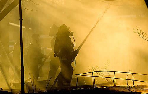 Firefighter Troutman spraying fire hose